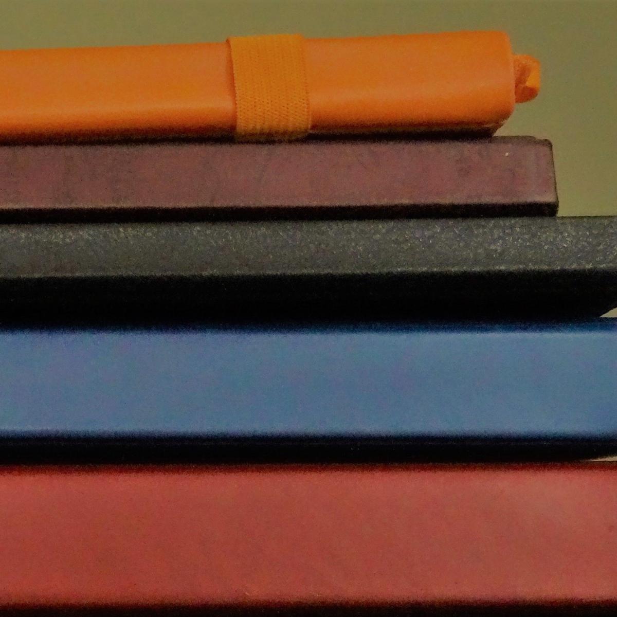 Close-up of multicoloured notebooks arranged like steps.